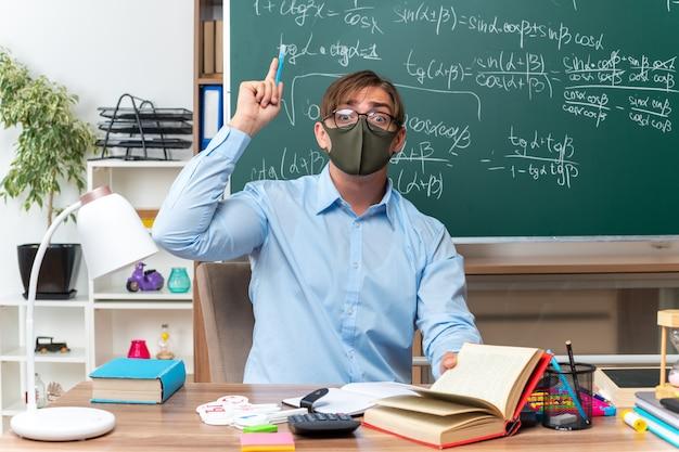 Junge männliche lehrer mit brille und gesichtsschutzmaske mit zeigefinger, der eine neue idee hat, die an der schulbank mit büchern und notizen vor der tafel im klassenzimmer sitzt