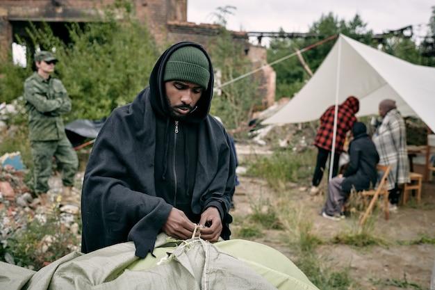 Junge männliche migranten schlagen zelt in flüchtlingscamping auf