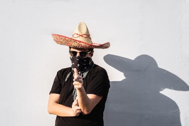 Junge männliche person gekleidet in traditionellem sombrero, kopftuch und sonnenbrille. mexikanisches festliches oder halloween-konzept des mannes, der sich als bandit oder gangster des westlichen stils ausgibt