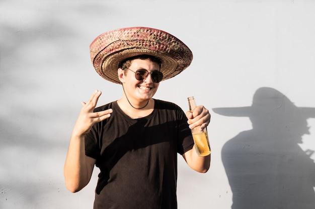 Junge männliche person in sombrero, die flasche des getränks hält. festliches konzept der mexiko-unabhängigkeit des mannes, der nationalen mexikanischen hut feiert, der feiert