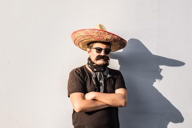 Junge männliche person verkleidet in traditionellem mexikanischen sombrero, falschem schnurrbart, kopftuch und sonnenbrille. festival- oder halloween-konzept des mannes, der sich als bandit oder gangster des westlichen stils ausgibt