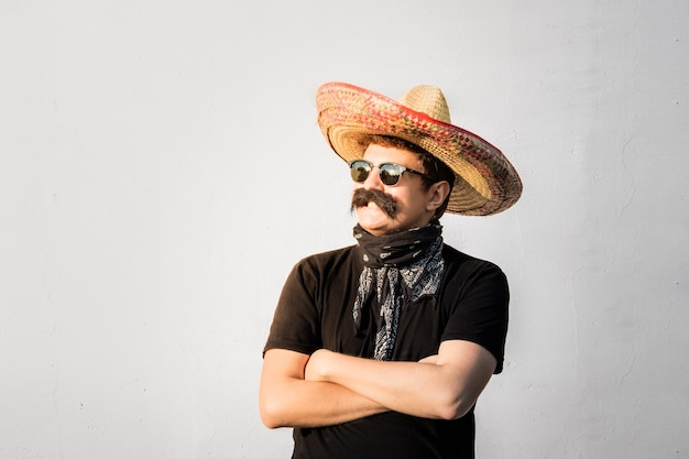 Junge männliche person verkleidet in traditionellem mexikanischen sombrero, falschem schnurrbart, kopftuch und sonnenbrille. festliches oder halloween-konzept des mannes, der sich als bandit oder gangster des westlichen stils ausgibt