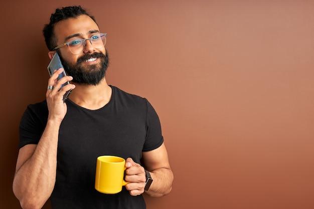 Junge männliche sprechen am telefon, indischer arabischer mann der gemischten rasse trinken tee