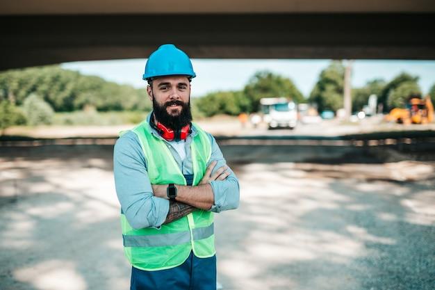Junge männliche straßenbauarbeiter bei seiner arbeit. er steht, posiert und schaut mit verschränkten armen in die kamera. heller sonniger tag. starkes licht.