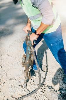Junge männliche straßenbauarbeiter bei seiner arbeit. heller sonniger tag. starkes licht.