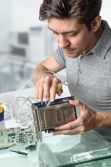 Junge männliche technologie säubert fehlerhaften computerprozessor