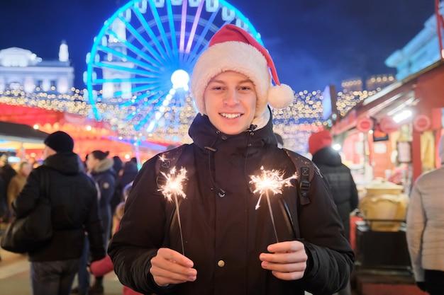 Junge männliche teenager in weihnachtsmütze mit brennenden wunderkerzen in die kamera schauen, gratulieren. junge am weihnachtsmarkt, hintergrund funkelnde lichter der girlanden der abendstadt, riesenrad