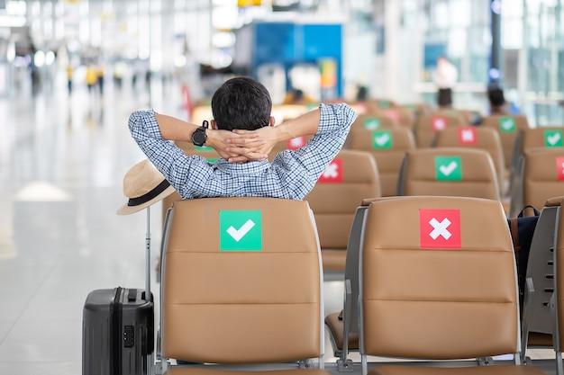 Junge männliche tragen gesichtsmaske, die auf stuhl im flughafenterminal sitzt