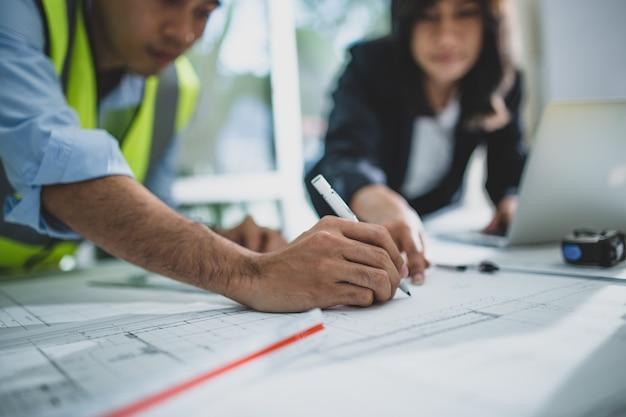 Junge männliche und weibliche architektenkollegen zeichnen grafische planung des innenarchitekturprojekts, das mit talentiertem lehrer zusammenarbeitet, der ratschläge gibt und fehler während der trainingsstunde korrigiert