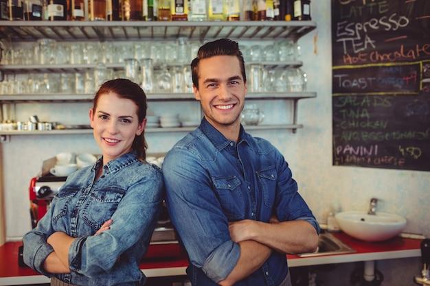 Junge männliche und weibliche baristas in der cafeteria