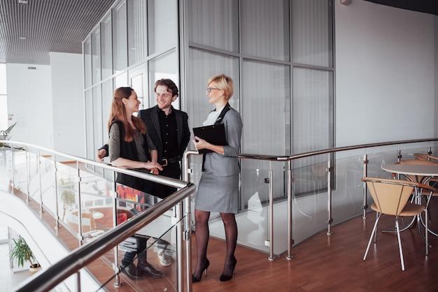 Junge männliche und weibliche mitarbeiter, die produktiven arbeitsprozess im büro, lächelnde studenten besprechen und planen