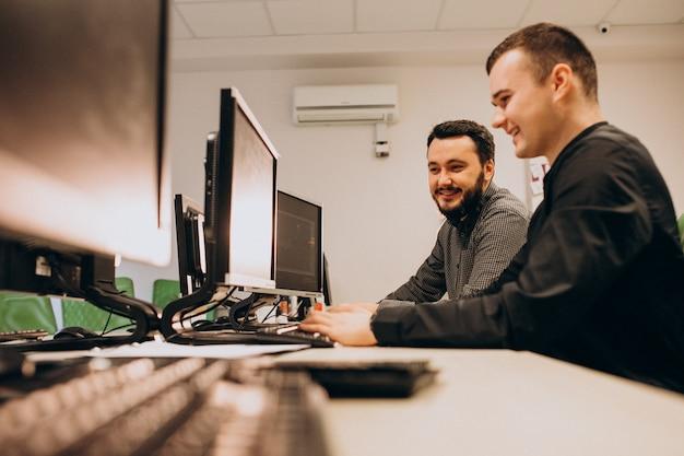 Junge männliche webdesigner, die an einem computer arbeiten
