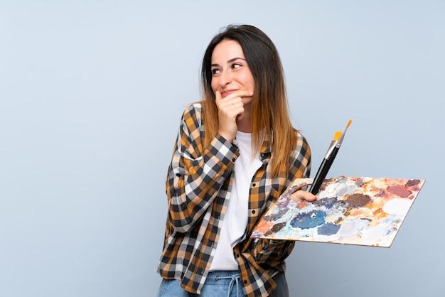 Junge malerfrau über lokalisierter blauer wand eine idee denkend und seite schauend