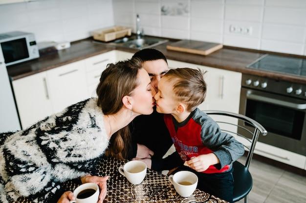 Junge mama, papa und junge trinken morgens kaffee und tee. familien-, ess- und personenkonzept.