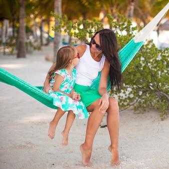 Junge mama und kleines mädchen auf den tropischen ferien, die in der hängematte sich entspannen