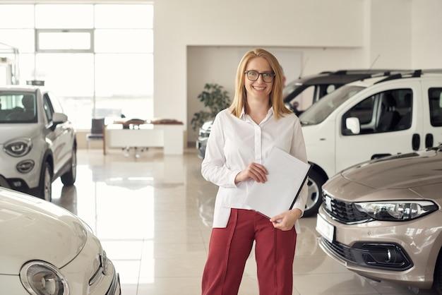 Junge managerin lädt in den ausstellungsraum ein, um sich neue autos anzuschauen.