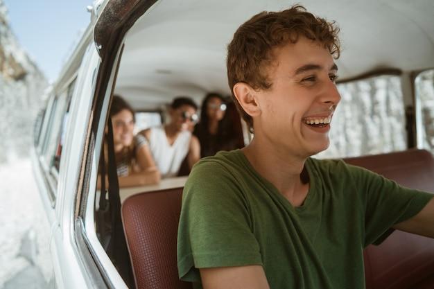 Junge mann fahrer genießen eine reise mit einem lächeln zum strand gehen