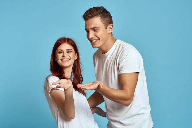 Junge mann und frau paar in weißen t-shirts auf einer hellblauen wand