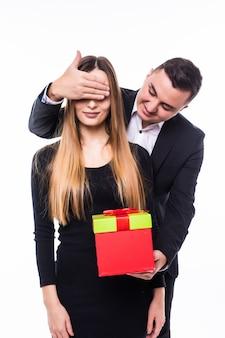Junge mann und mädchenpaar präsentieren geschenk schließen augen mit einer hand
