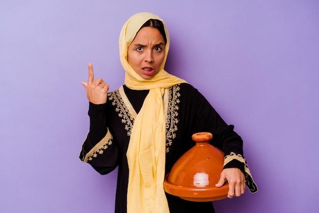 Junge marokkanische frau, die eine tajine lokalisiert auf lila hintergrund hält, die eine enttäuschungsgeste mit zeigefinger zeigt.
