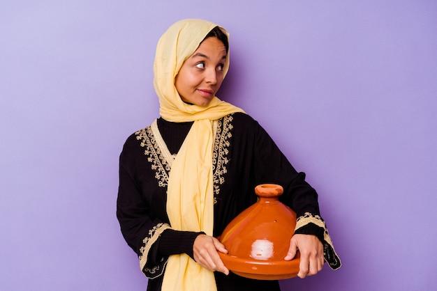Junge marokkanische frau, die eine tajine lokalisiert auf lila hintergrund hält, schaut lächelnd, fröhlich und angenehm beiseite.