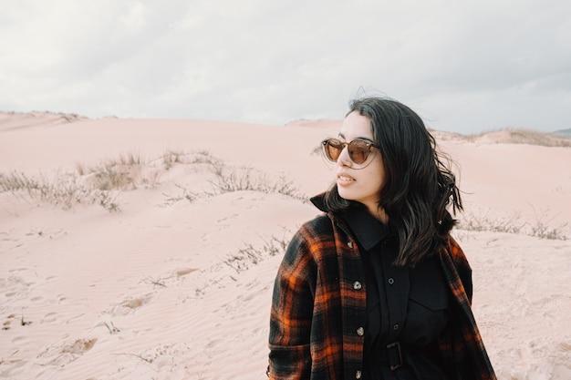 Junge marokkanische frau, die mit sonnenbrille von einigen dünen am strand wegschaut