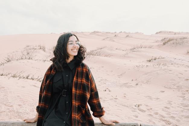 Junge marokkanische frau lächelnd weg von einigen dünen am strand schauend