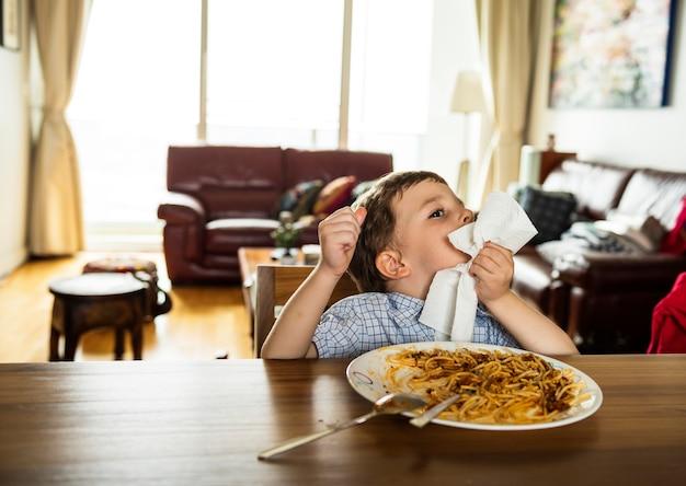 Junge mealtome, das zu hause spaghettis isst