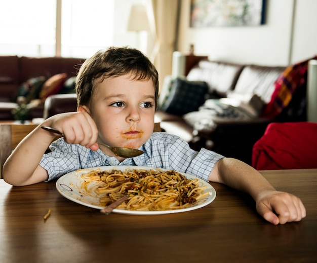 Junge mealtome, die zu hause spaghettis essen