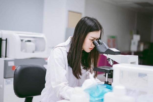 Junge medizinische wissenschaftlerin, die mikroskop im labor betrachtet