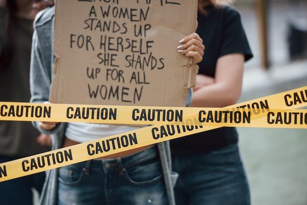 Junge menge. eine gruppe feministischer frauen protestiert im freien für ihre rechte
