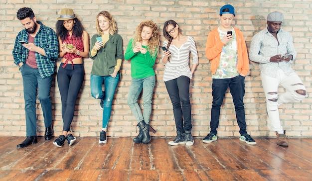 Junge menschen, die auf mobiltelefone herabblicken - jugendliche, die sich an eine wand lehnen und mit ihren smartphones sms schreiben - konzepte über technologie und globale kommunikation