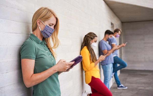 Junge menschen, die gesichtsschutzmasken mit smartphones tragen und dabei soziale distanz halten