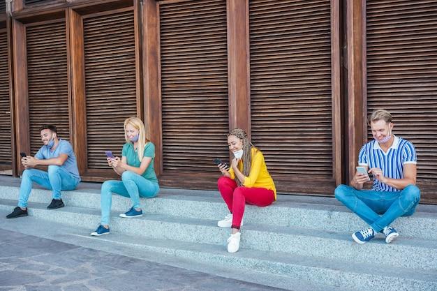 Junge menschen, die gesichtsschutzmasken mit smartphones tragen und gleichzeitig während der coronavirus-zeit soziale distanz halten