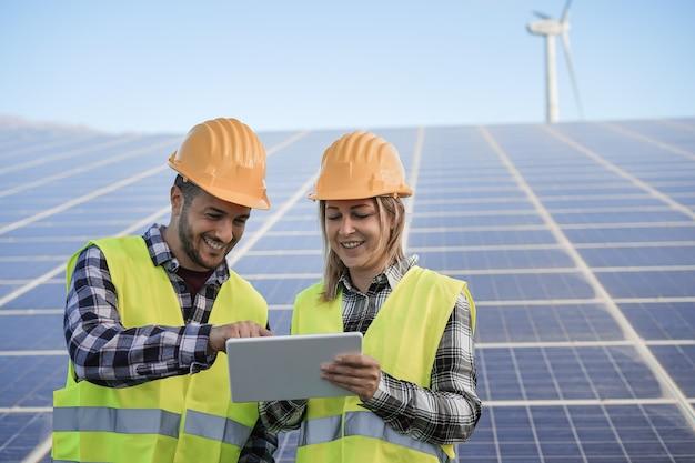 Junge menschen, die mit digitalen tablets auf einem bauernhof für erneuerbare energien arbeiten - konzentrieren sie sich auf gesichter