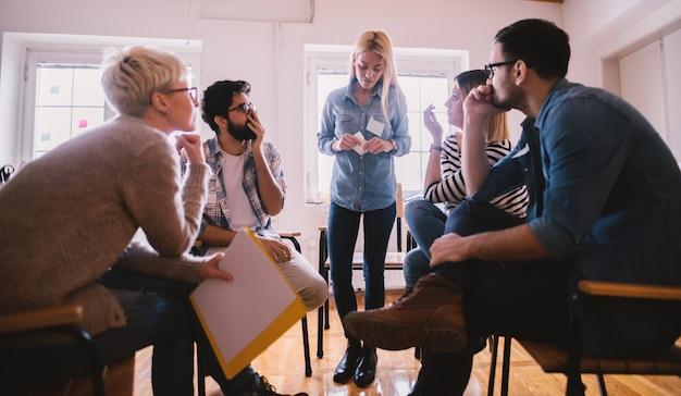 Junge menschen mit problemen, die auf das geständnis ihrer nervösen freundin mit schockreaktion hören, während sie zusammen auf einer speziellen gruppentherapie sitzen.
