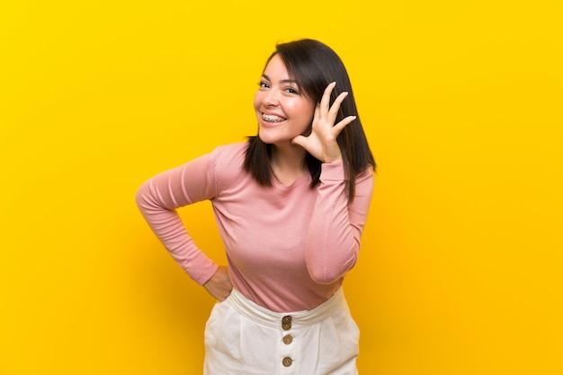 Junge mexikanerin über lokalisiertem gelb etwas hörend, indem hand auf das ohr gesetzt wird