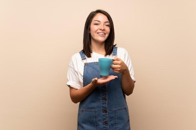 Junge mexikanerin über lokalisiertem haltenem heißem tasse kaffee