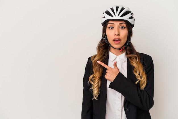 Junge mexikanische frau, die ein fahrrad reitet, um lokal auf weißer wand zu arbeiten, die zur seite zeigt