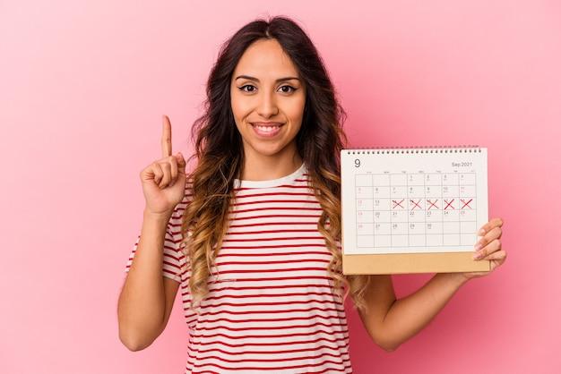 Junge mexikanische frau, die einen kalender hält, der auf rosafarbenem hintergrund isoliert ist und die nummer eins mit dem finger zeigt.