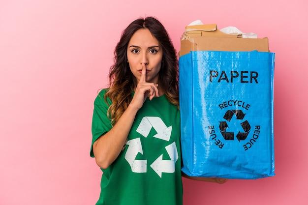 Junge mexikanische frau, die pappe einzeln auf rosafarbenem hintergrund recycelt, hält ein geheimnis oder bittet um stille.