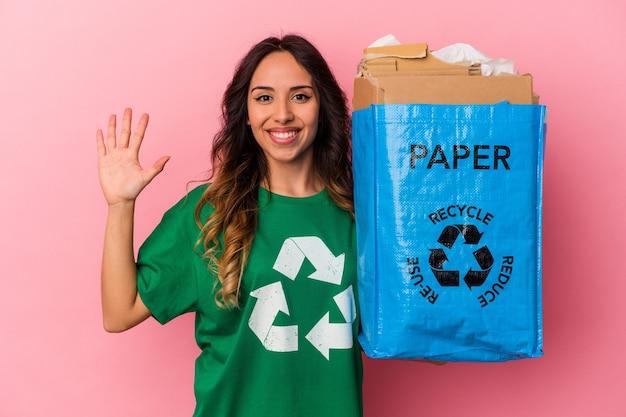 Junge mexikanische frau, die pappe einzeln auf rosafarbenem hintergrund recycelt, lächelt fröhlich und zeigt nummer fünf mit den fingern.