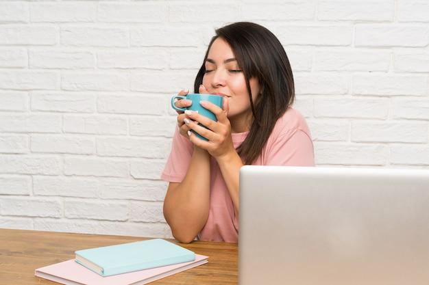 Junge mexikanische frau mit einem laptop, der einen tasse kaffee hält