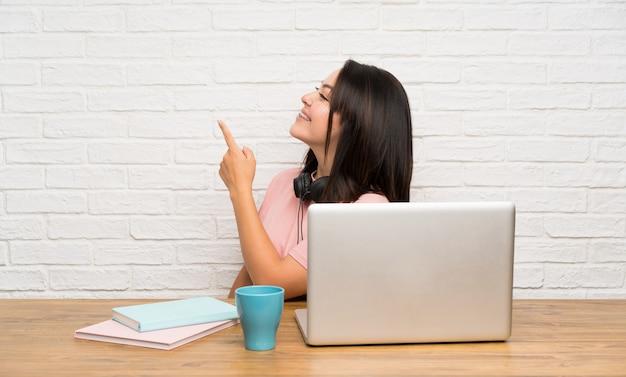 Junge mexikanische frau mit einem laptop zurück zeigend mit dem zeigefinger