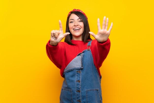 Junge mexikanische frau mit overall über der gelben wand, die sieben mit den fingern zählt