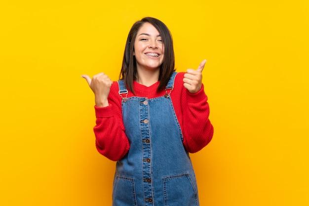 Junge mexikanische frau mit overall über gelber wand mit den daumen herauf geste und das lächeln