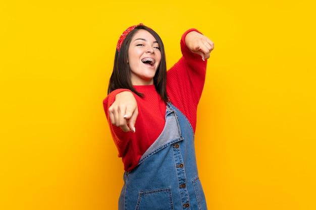 Junge mexikanische frau mit overall über gelber wand zeigt finger auf sie beim lächeln