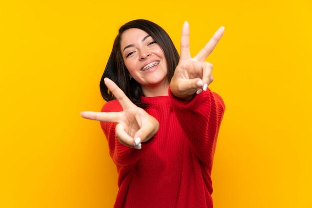 Junge mexikanische frau mit roter strickjacke über gelber wand lächelnd und siegeszeichen zeigend
