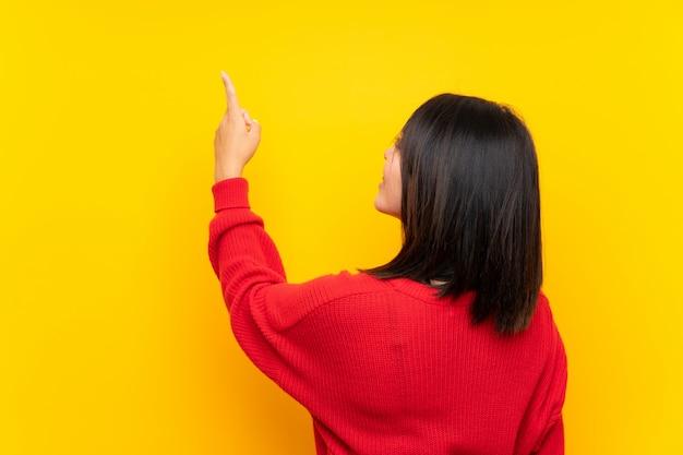 Junge mexikanische frau mit roter strickjacke über gelber wand zurück zeigend mit dem zeigefinger