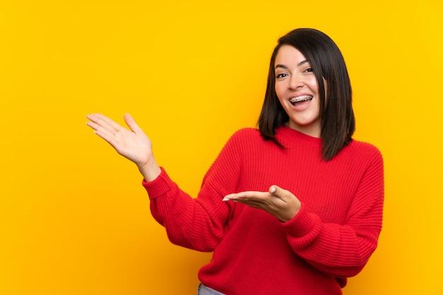 Junge mexikanische frau mit roter strickjacke über verlängerungshänden der gelben wand zur seite, damit die einladung kommt